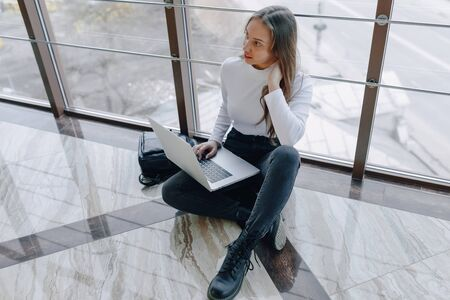 attractive girl working with laptop and things in airport terminal or office on floor. travel atmosphere or alternative work atmosphere. freelancer student travels to business meeting. concept of alternative workplace, technology and waiting. Imagens