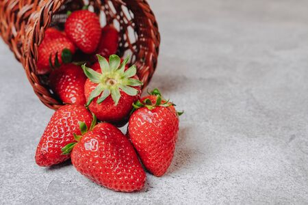 juicy strawberries poured out chaotically on a concrete light background. delicious fruits in summer season. natural products and natural resources. simple picture.
