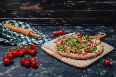 delicious Neapolitan pizza on a blackboard with cherry tomatoes, free space for text