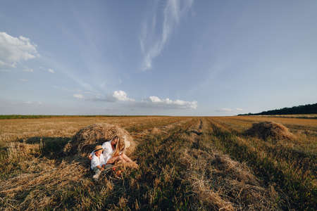 pretty blond long-haired woman with little blond son at sunset relaxing in the field and savoring fruit from a straw basket. summer, farming, nature and fresh air in the countryside. sunset. Imagens