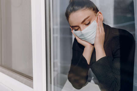 young attractive girl in a protective medical mask looks out the window. isolation during the epidemic. medical home isolation.