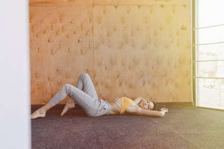 Cozy young attractive girl doing fitness exercises with yoga on the floor on a wooden background at gym