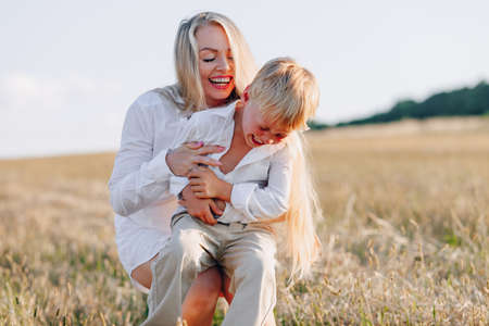 blond little boy playing with mom with white hair with hay in field. summer, sunny weather, farming. happy childhood. family.