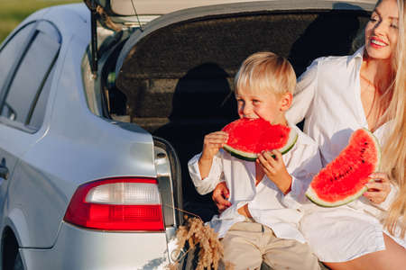 pretty blond hair woman with little blond son at sunset relaxing behind the car and eating watermelon. summer, travel, nature and fresh air in the countryside. sunset. Imagens