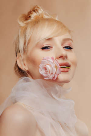 pretty attractive girl with blond hair, fashion shooting, rose, simple background, studio