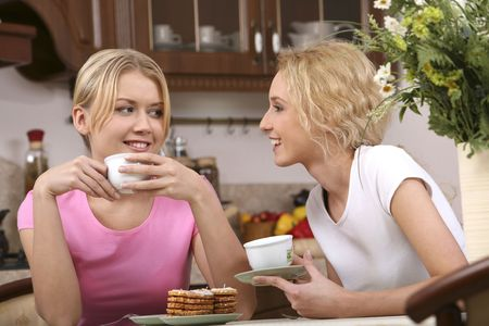 confide: Two smiling girls have tea with tasty cookies in the kitchen