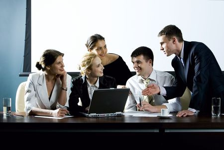 Large group of young businessman gathered together around the laptop discussing interesting question photo