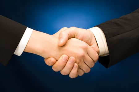 Business handshake - making a deal over a blue background Stock Photo - 2427042