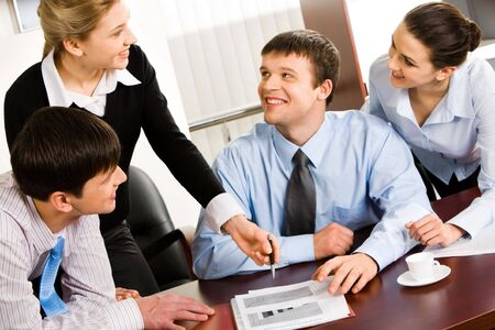 affair: Four smiling business people discussing an affair