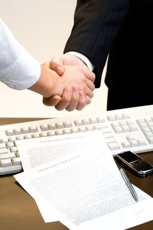 Two business people shaking hands on the background of the keyboard and the signed contract photo
