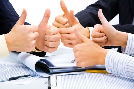 thumbs up symbol: Three people holding their thumbs up meaning a great business plan Stock Photo
