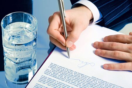 signing a contract: Horizontal photo of a businessman�s hands signing a contract with a glass of water on the backgrounds