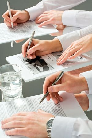 Hands of three business people over the documents lying on the table with a glass of water near by Stock Photo - 2430158