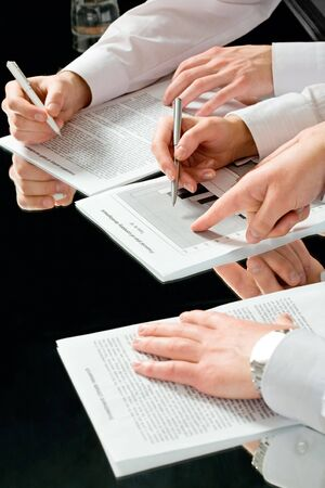 Image of male hand pointing at a document at business meeting  photo