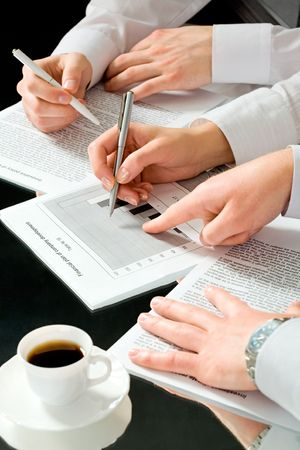 Image of business people�s hands during discussion of business documents with a cup of coffee near by photo