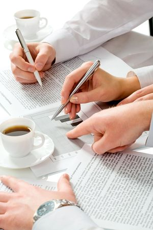Close-up of teamwork: business people�s hands pointing at the paperwork  photo
