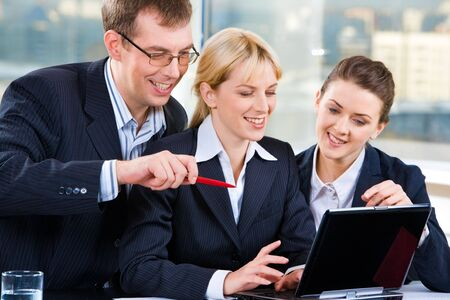 Three business people sitting at the table and looking into the screen of a laptop with smiles Stock Photo - 2428996