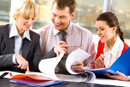 Two business ladies and a businessman looking through their business documents and discussing them smiling Stock Photo - 2428997