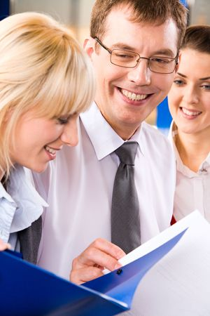 Image of two business ladies and a businessman reading and discussing business plans happily smiling Stock Photo - 2428993