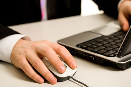 Human hands touching computer mouse and keys of opened laptop Stock Photo - 2430142