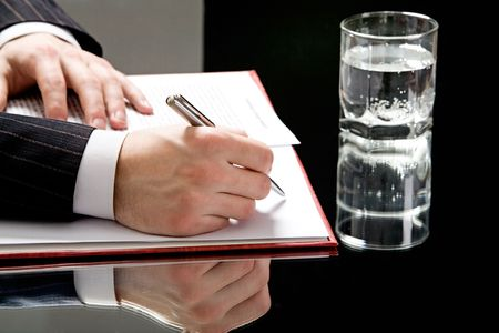 autograph: View of human hands on with a pen ready to write with a glass of water standing near by Stock Photo
