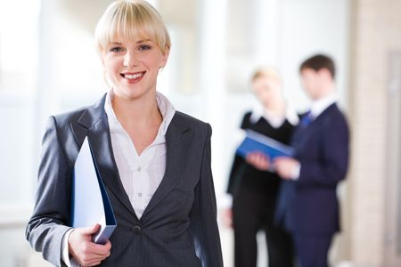 Portrait of young pretty professional holding a folder on the background of people  Stock Photo - 2444437