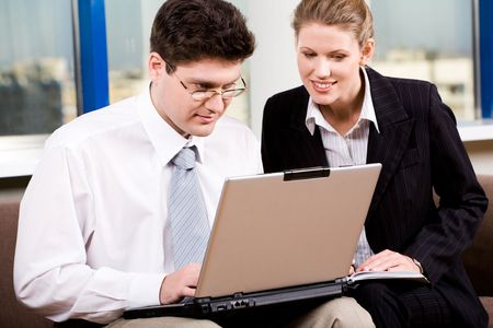 Businessman in eyeglasses and woman are looking at the monitor of laptop Stock Photo - 2432342