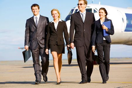 airport business: Group of successful people walking on the background of the airplane
