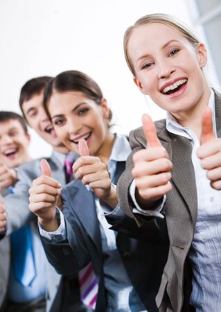 Vertical image of business people giving the thumbs-up sign Stock Photo - 2432983