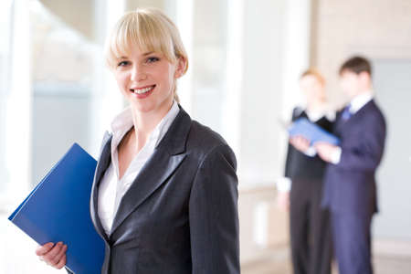 Attractive specialist in suit holding a grey folder on the background of people  Stock Photo - 2432981