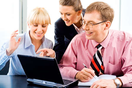 Business woman is explaining the correct way of analysis to his colleagues pointing at the monitor of laptop photo