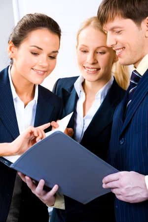 Team of three people discussing an important document at business meeting Stock Photo - 2455711