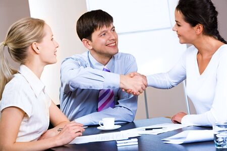 concluding: Portrait of woman and man concluding a bargain at business meeting