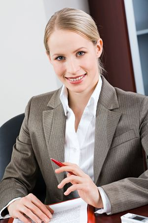 bossy: Portrait of bossy woman sitting at a table and looking at camera Stock Photo