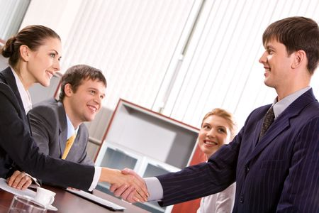 businesswear: Businessman and woman shaking hands at meeting in the office