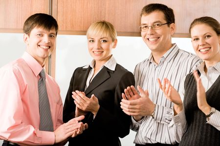 Portrait of four business people smiling and applauding in the office Stock Photo - 2464883