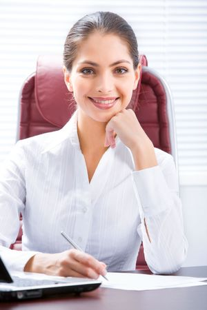 leans: Attractive business woman leans her elbow on a table