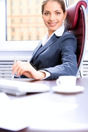 Image of self-confident manager sitting at the table in the office photo