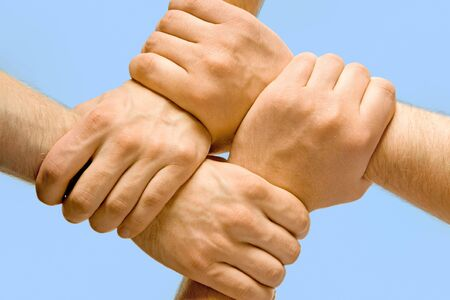 strength in unity: Image of crossed hands isolated over blue background
