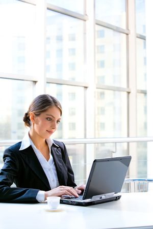 Portrait of confident business woman sitting at the table and typing a document on the laptop  photo