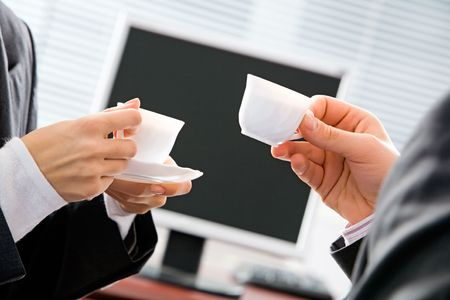 Portrait of two business people�s hands holding cups on the background of screen  Stock Photo