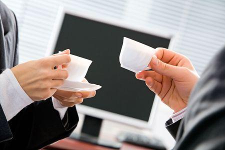 dialogo: Retrato de dos manos de la gente del negocio que sostienen las tazas en el fondo de la pantalla