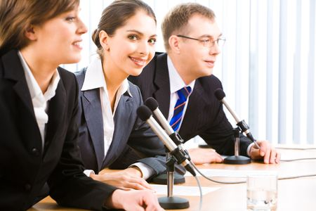 Portrait of confident professionals sitting at the table with microphones, papers and glass on it   photo