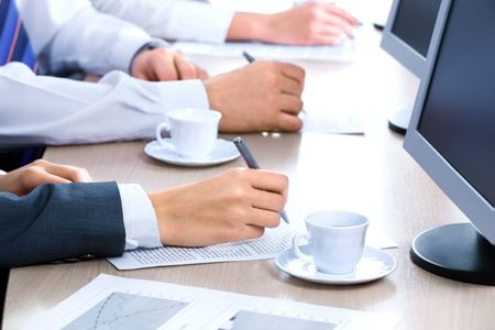 educating: Hands of three business people over the documents lying on the table with cups and monitors near by