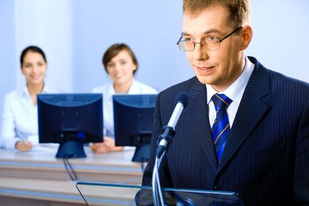 delivers: Successful business man delivers oneself of a speech at a conference