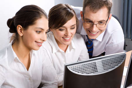 Team of business people looking at monitor of computer photo