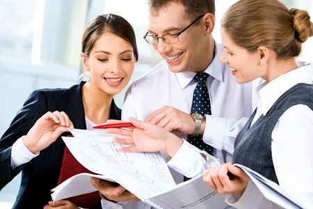 Image of three happy business people looking at business plan with smiles  photo