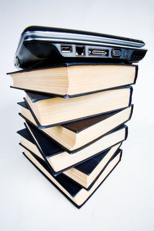 Image of pile of books with a black closed laptop on top photo