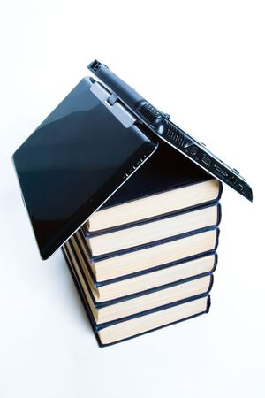 Symbol of house: stack of books with a black laptop on top photo