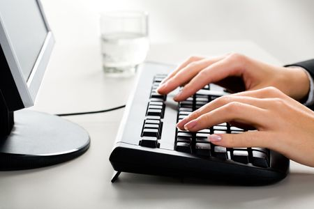 Photo of female hands on the keyboard of computer typing a letter photo